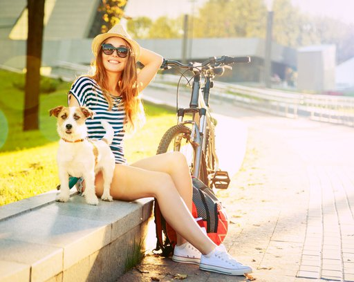 Smiling Hipster Girl with her Dog and Bike in City.